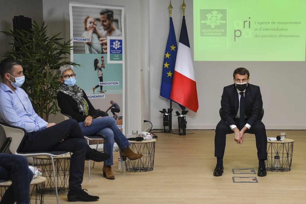 French President Emmanuel Macron, right, attends a meeting during a visit at the headquarters of the local CAF (French family allowance public service...