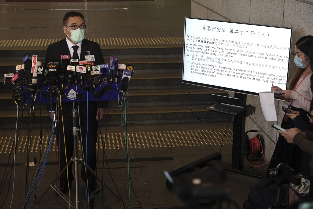 Senior superintendent of National Security Department Li Kwai-wah talks to reporters next to a TV screen displaying the National Security No. 22 durin...