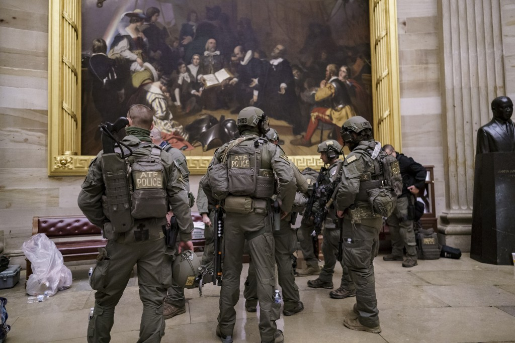 After violent protesters loyal to President Donald Trump stormed the U.S. Capitol today, a tactical team with ATF gathers in the Rotunda to provide se...