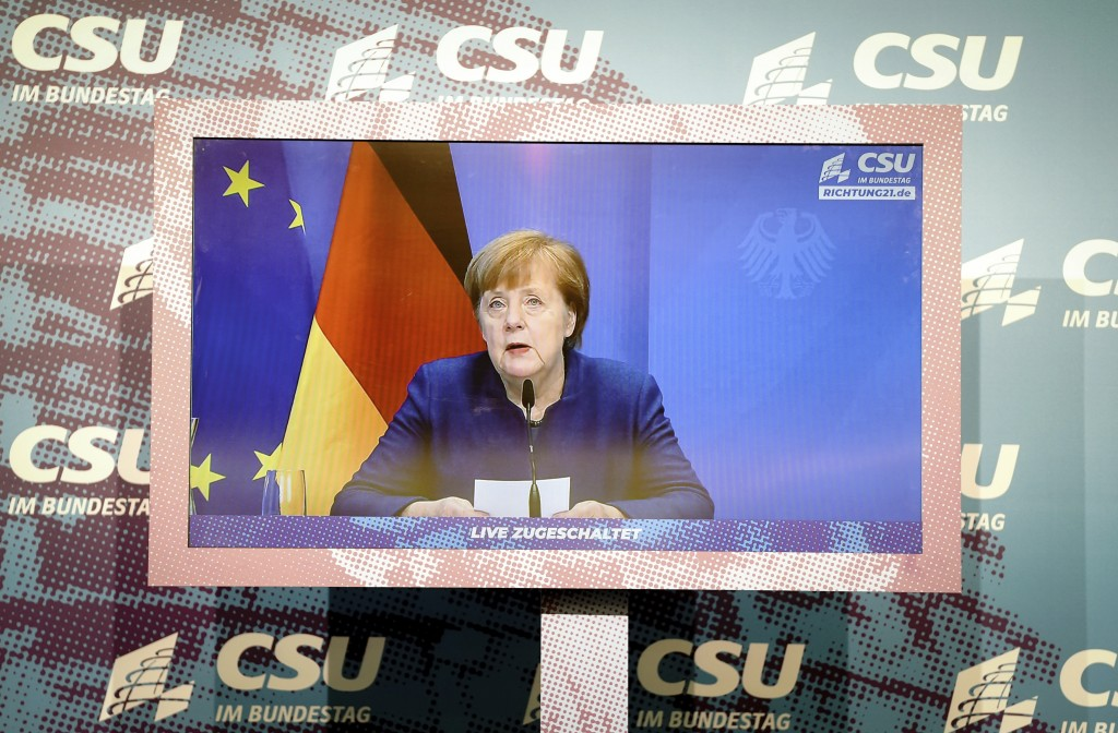 German Chancellor Angela Merkel is seen on a screen, making a statement on the events in Washington with the storming of the Capitol by Trump supporte...