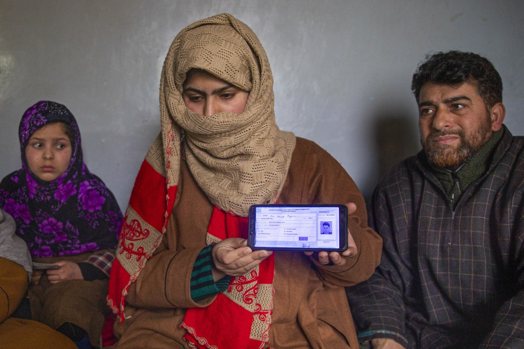Zarqa Mushtaq, center, shows on a mobile phone the 11th grade examination slip of her 16 -year old brother Athar Mushtaq, as her father Mushtaq Ahmad ...