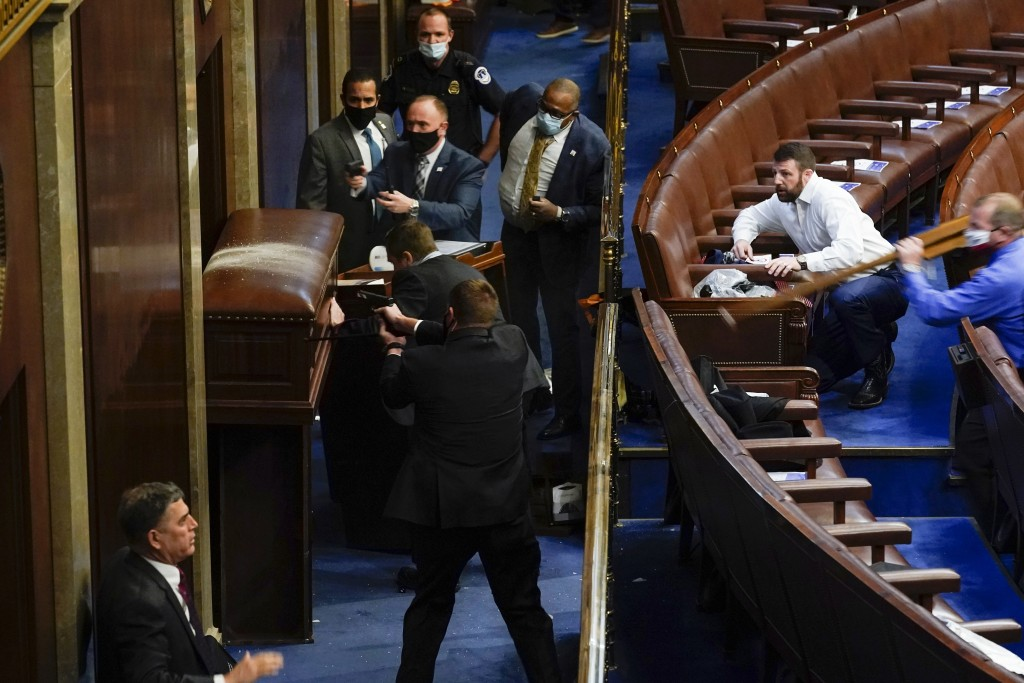 U.S. Capitol Police with guns drawn stand near a barricaded door as protesters try to break into the House Chamber at the U.S. Capitol on Wednesday, J...