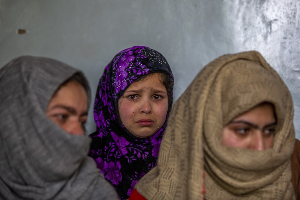 Tears roll down the cheeks of 7 year old Mahira Nazir, cousin of 16-year-old Athar Mushtaq, as the family talks to Associated Press in Bellow, south o...