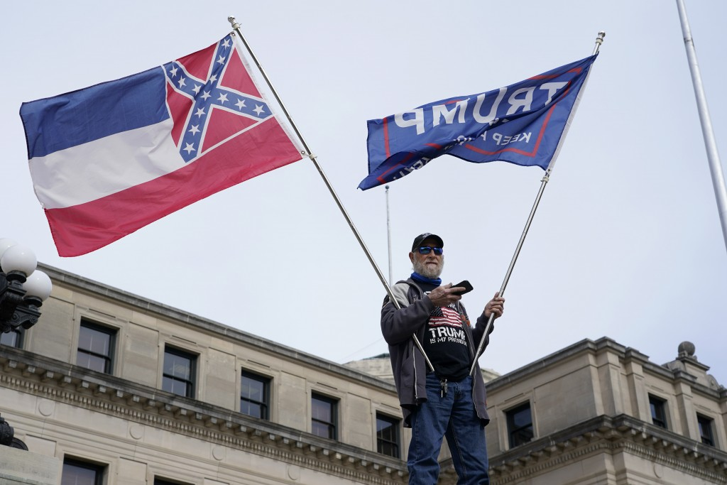 Lee Anglada of Biloxi, stands on the steps of the Mississippi Capitol and waves the retired state flag which incorporated a Confederate battle emblem ...