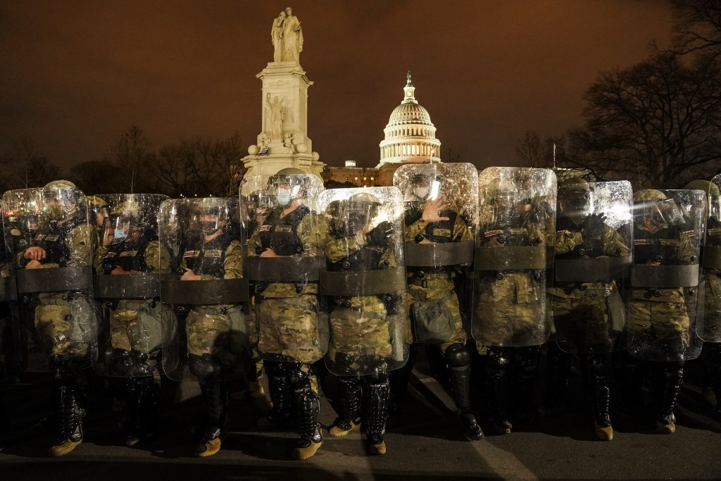 District of Columbia National Guard stand outside the Capitol, Wednesday night, Jan. 6, 2021, after a day of rioting protesters. It's been a stunning ...