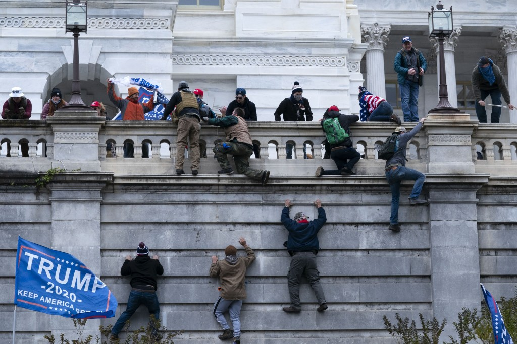 Supporters of President Donald Trump climb the West wall of the the U.S. Capitol on Wednesday, Jan. 6, 2021, in Washington. (AP Photo/Jose Luis Magana...