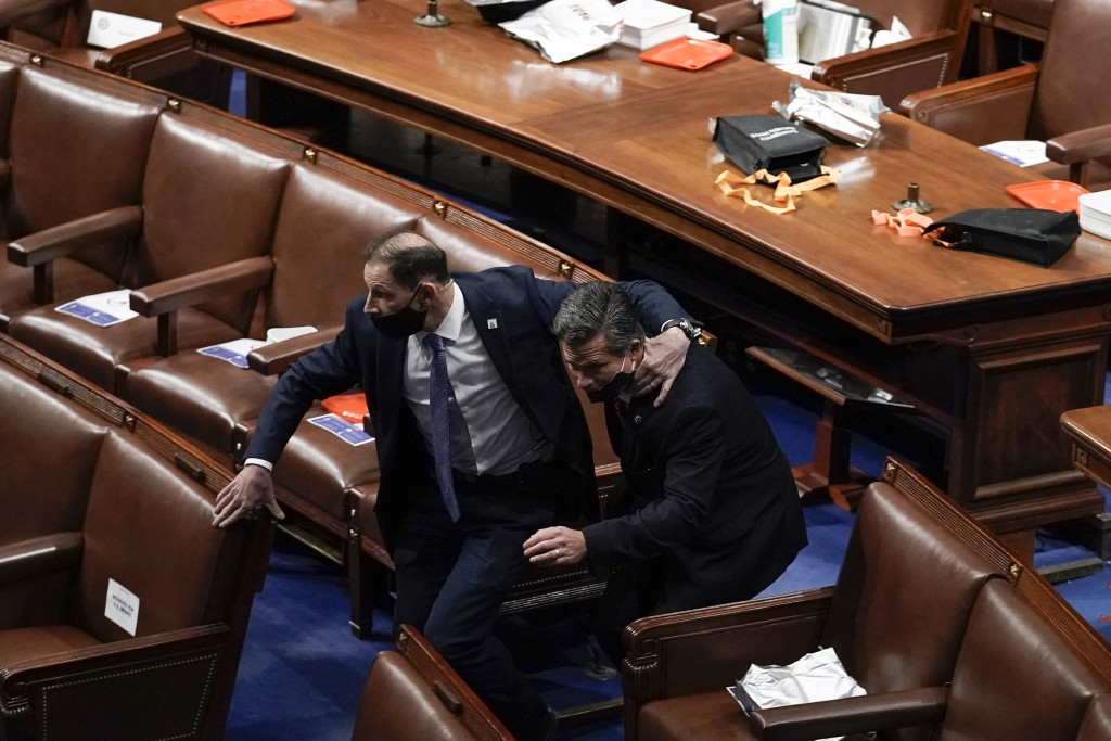Lawmakers evacuate the floor as protesters try to break into the House Chamber at the U.S. Capitol on Wednesday, Jan. 6, 2021, in Washington. (AP Phot...