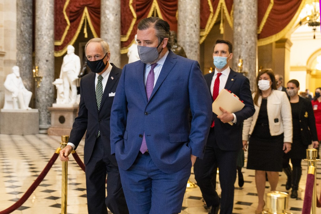 Sen. Ted Cruz, R-Texas, front, followed by Sen. Josh Hawley, R-Mo., walk from the House Chamber following a Senate procession carrying boxes holding E...
