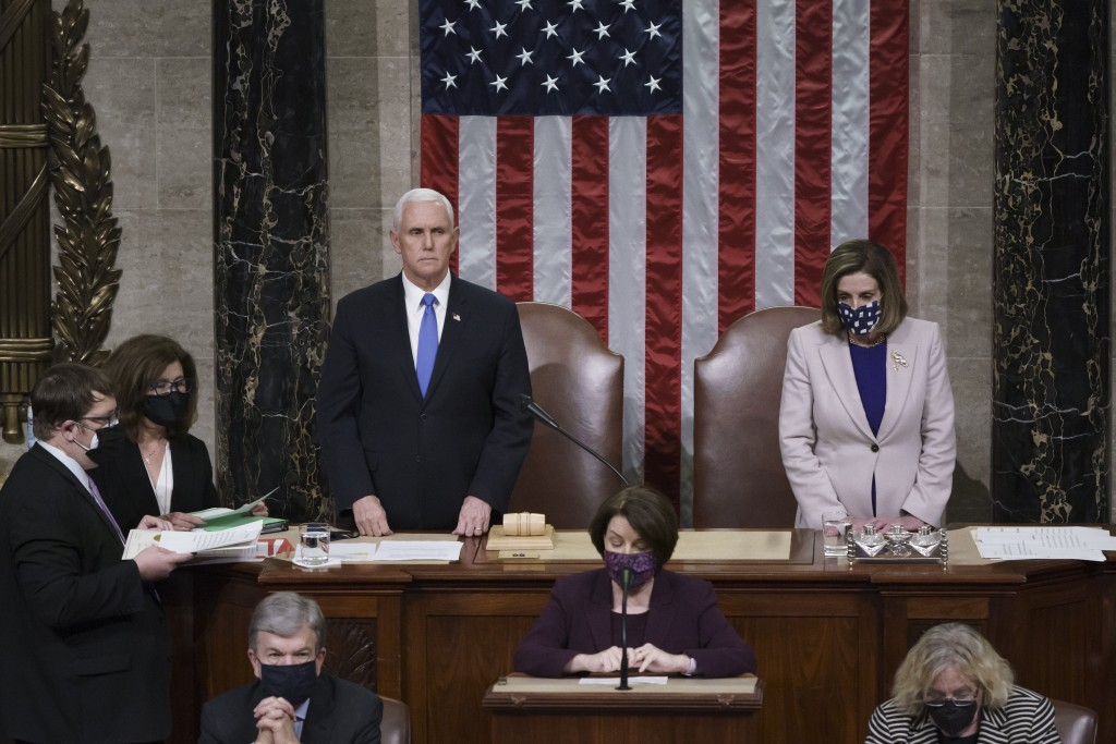 Vice President Mike Pence and Speaker of the House Nancy Pelosi, D-Calif., read the final certification of Electoral College votes cast in November's ...