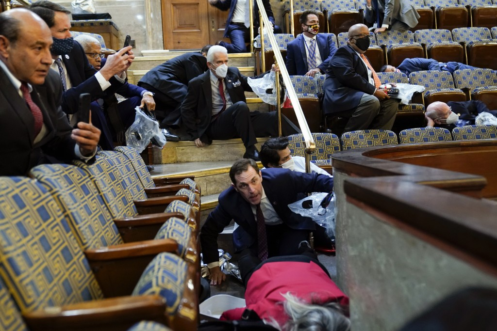People shelter in the House gallery as protesters try to break into the House Chamber at the U.S. Capitol on Wednesday, Jan. 6, 2021, in Washington. (...