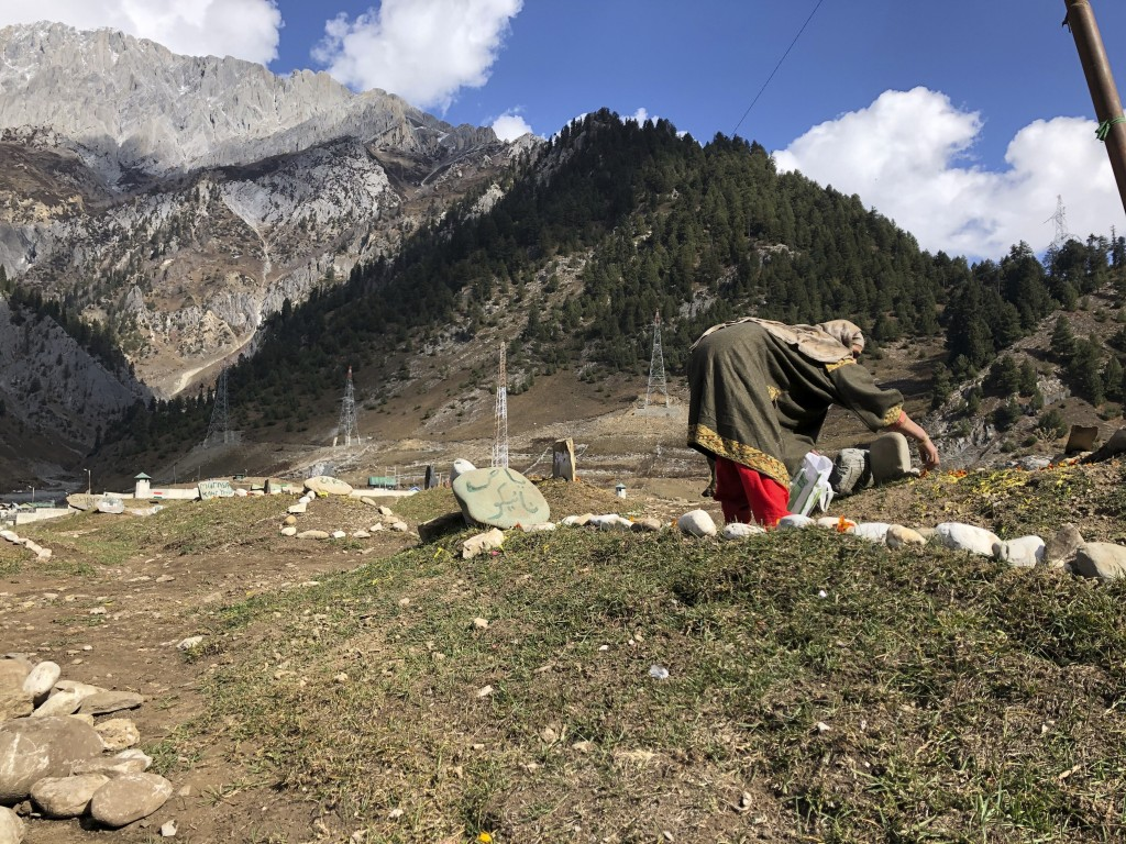 A woman offers flowers as relatives of suspected rebels killed by government forces visit a graveyard in Sonamarg, a remote mountainous resort in Indi...