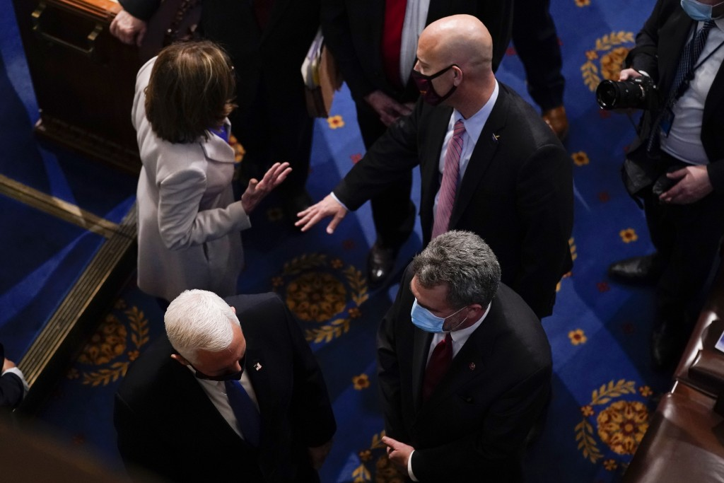 Vice President Mike Pence, bottom left, talks as House Speaker Nancy Pelosi, D-Calif., talks with Pence's chief of staff Marc Short after the final ce...