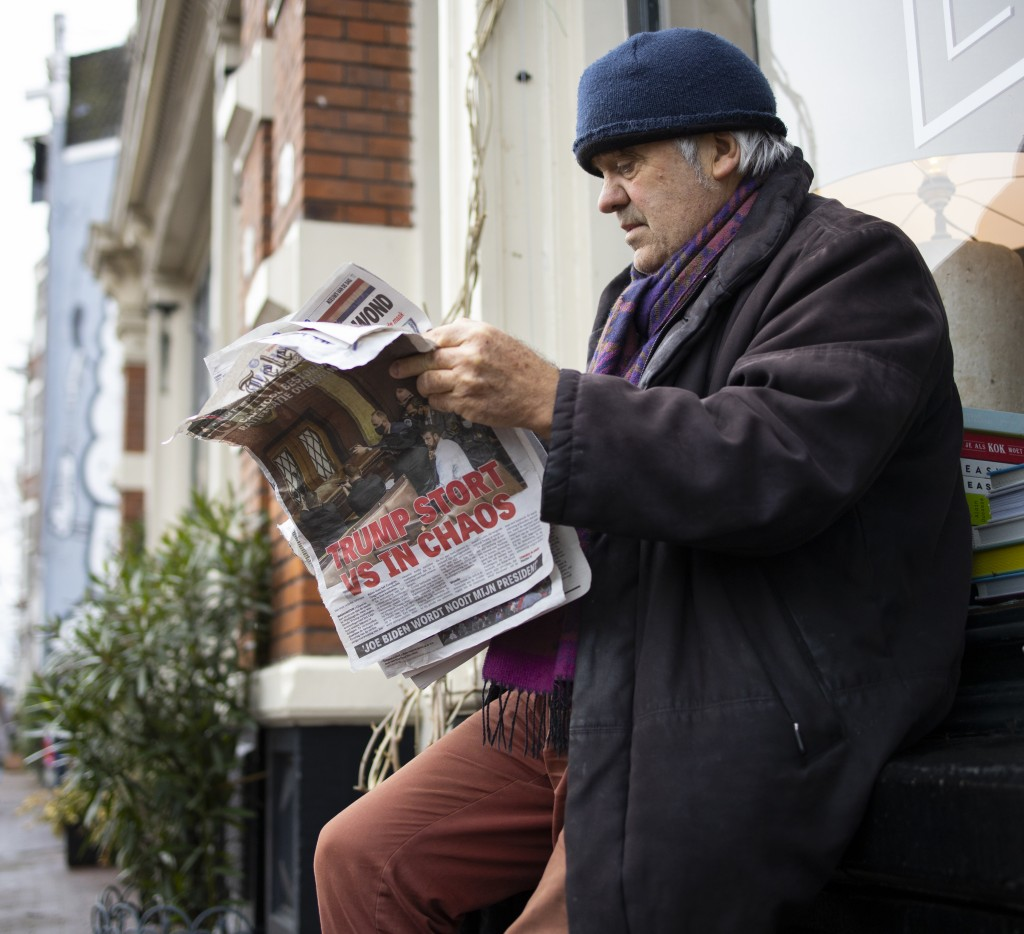 """A man reads a newspaper with a headline reading """"Trump Plunges U.S. into Chaos"""" outside a takeaway cafe in the center of Amsterdam, Netherlands, Thurs..."""