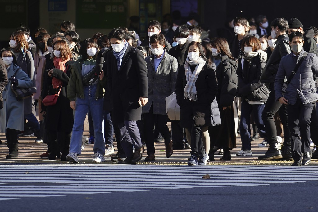 People wearing protective masks to help curb the spread of the coronavirus walk along pedestrian crossings in the Shibuya area of Tokyo Thursday, Jan....