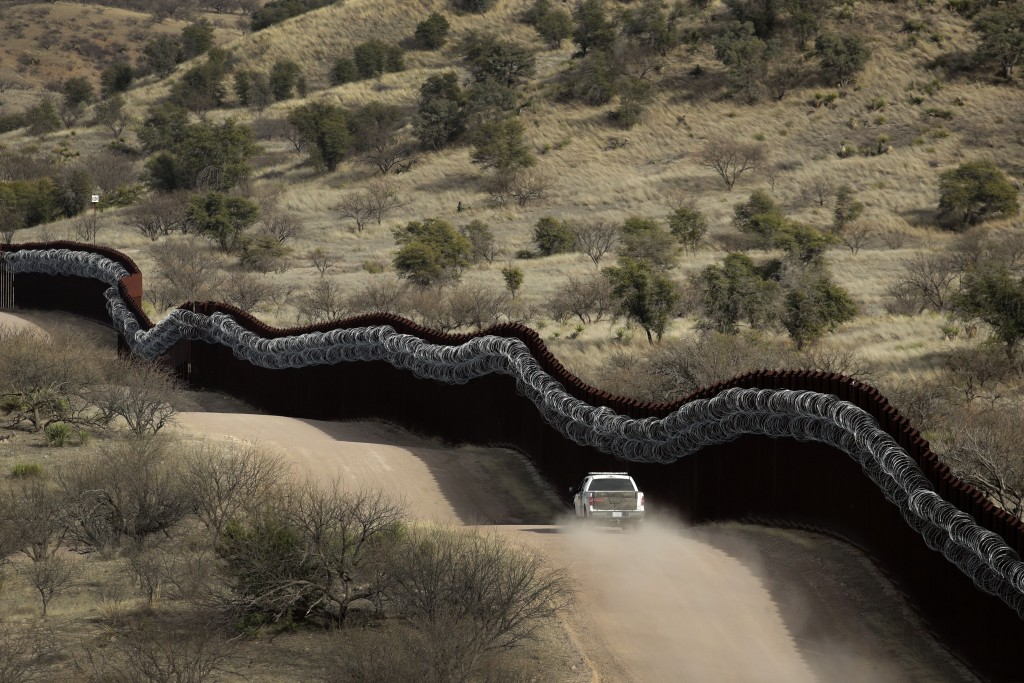 FILE - In this March 2, 2019, file photo, a Customs and Border Control agent patrols on the U.S. side of a razor-wire-covered border wall along Mexico...