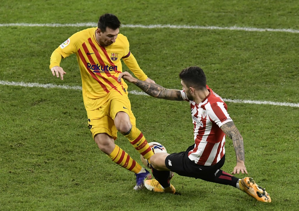 Barcelona's Lionel Messi, left, runs with the ball during the Spanish La Liga soccer match between Athletic Bilbao and Barcelona at San Mames stadium ...