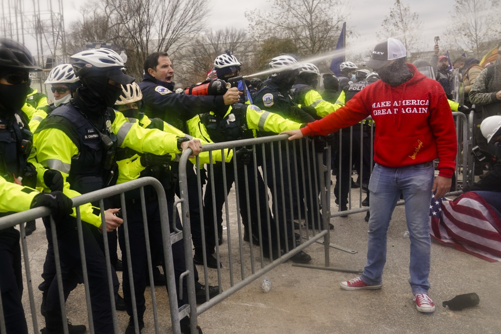 Demonstators loyal to President Donald Trump, are sprayed by police, Wednesday, Jan. 6, 2021, during a day of rioting at the Capitol. It's been a stun...