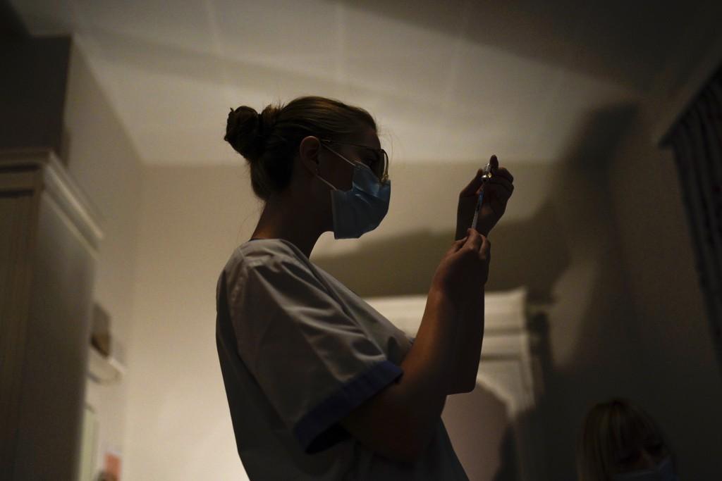 A nurse prepares a syringe with the Pfizer/Biontech COVID-19 vaccine at the CHC Landenne care home in Landenne-sur-Meuse, near Namur, Belgium, Thursda...