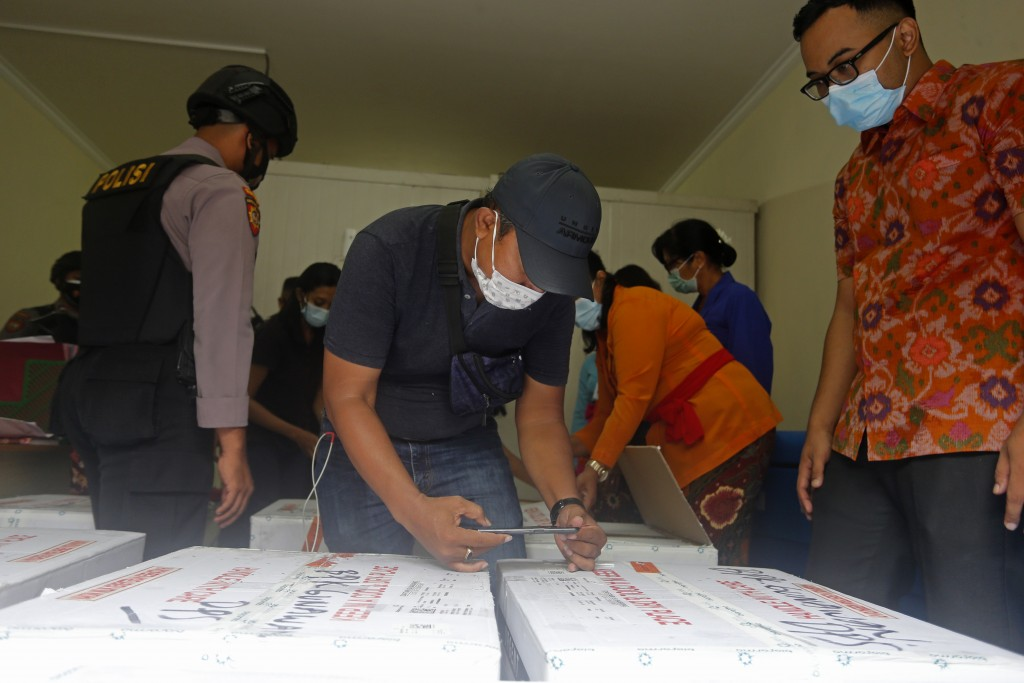 Health workers check the boxes containing coronavirus vaccines developed by China's Sinovac Biotech as they arrived in Bali, Indonesia on Thursday, Ja...