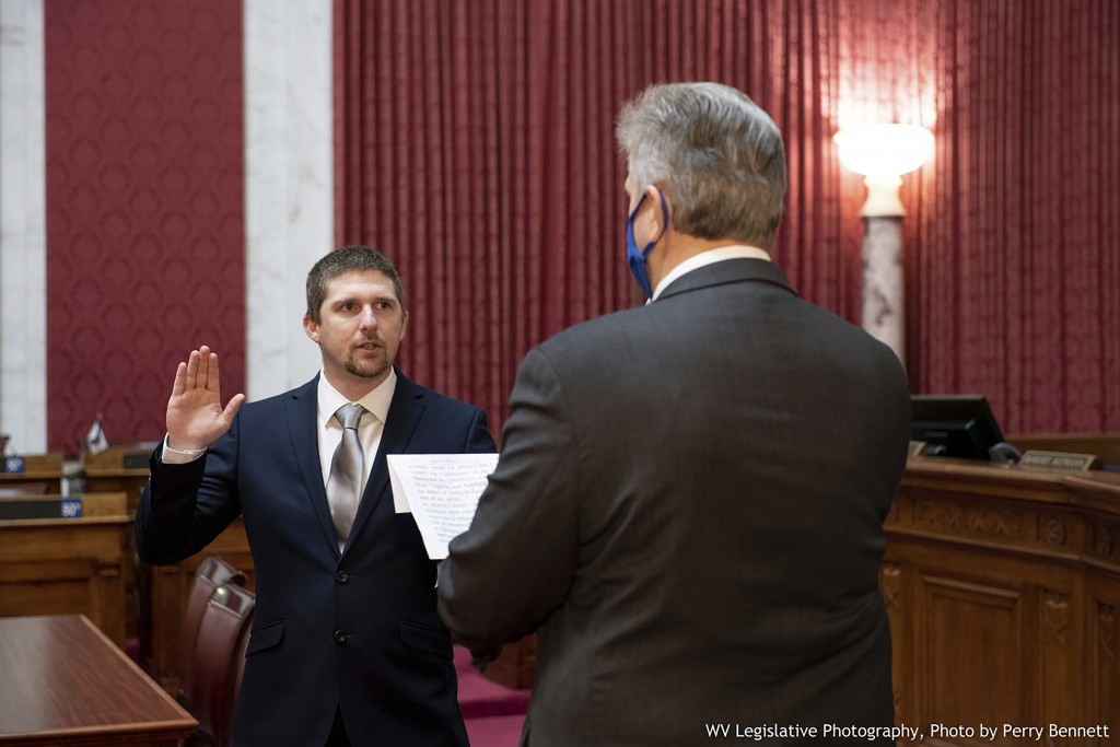 West Virginia House of Delegates member Derrick Evans, left, is given the oath of office Dec. 14, 2020, in the House chamber at the state Capitol in C...
