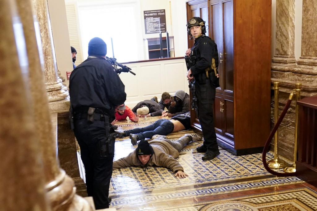 U.S. Capitol Police hold protesters at gun-point near the House Chamber inside the U.S. Capitol on Wednesday, Jan. 6, 2021, in Washington. (AP Photo/A...