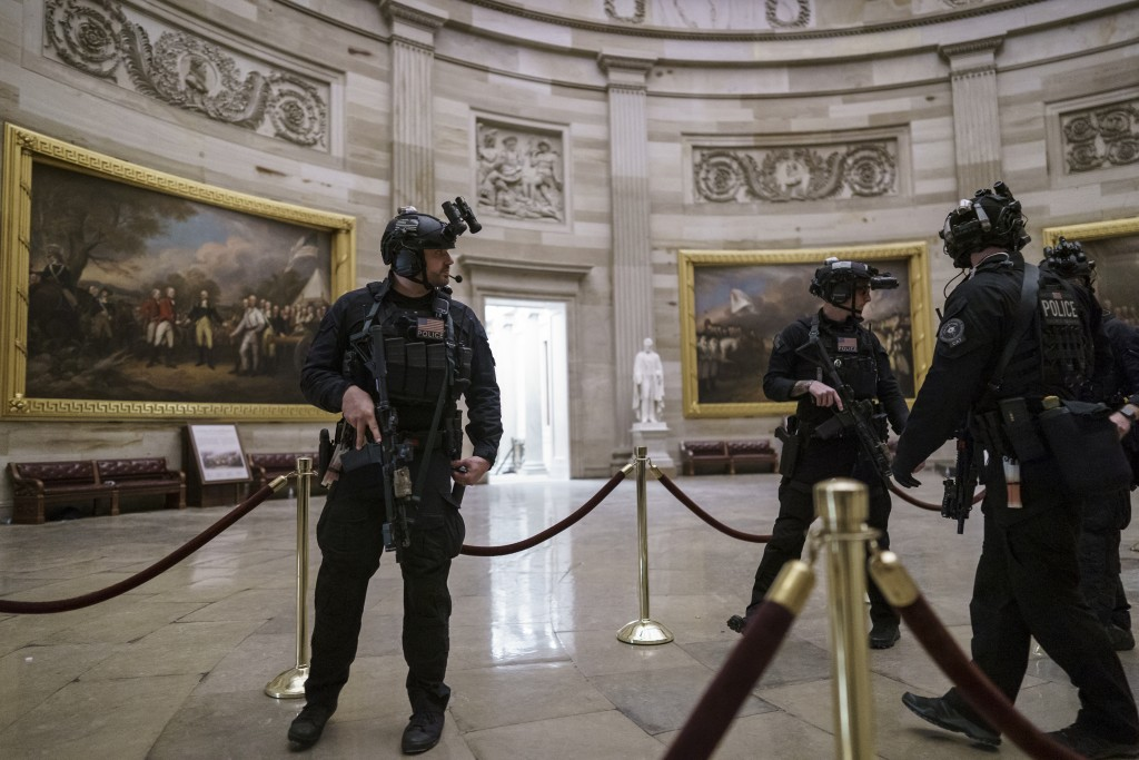 Members of the U.S. Secret Service Counter Assault Team walk through the Rotunda as they and other federal police forces responded as violent proteste...