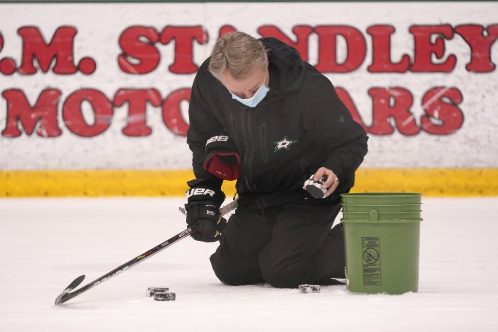 Dallas Stars head coach Rick Bowness picks up pucks between drills during NHL hockey training camp practice Wednesday, Jan. 6, 2021, in Frisco, Texas....