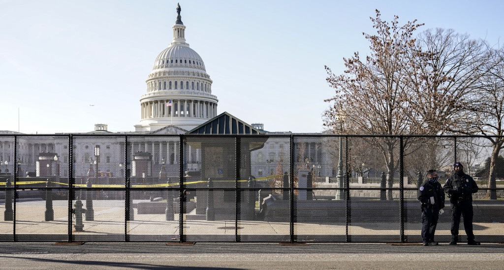 Capitol police officers stand outside of fencing that was installed around the exterior of the Capitol grounds, Thursday, Jan. 7, 2021 in Washington. ...