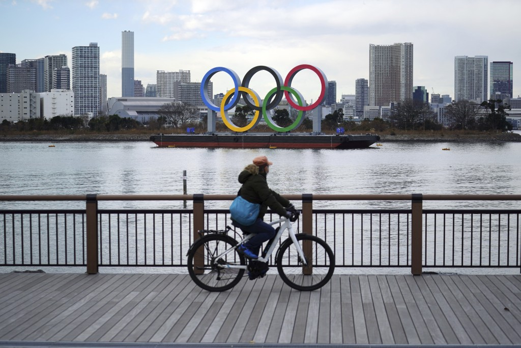 A man rides a bicycle near the Olympic rings floating in the water in the Odaiba section Friday, Jan. 8, 2021 in Tokyo. The senior member of the Inter...