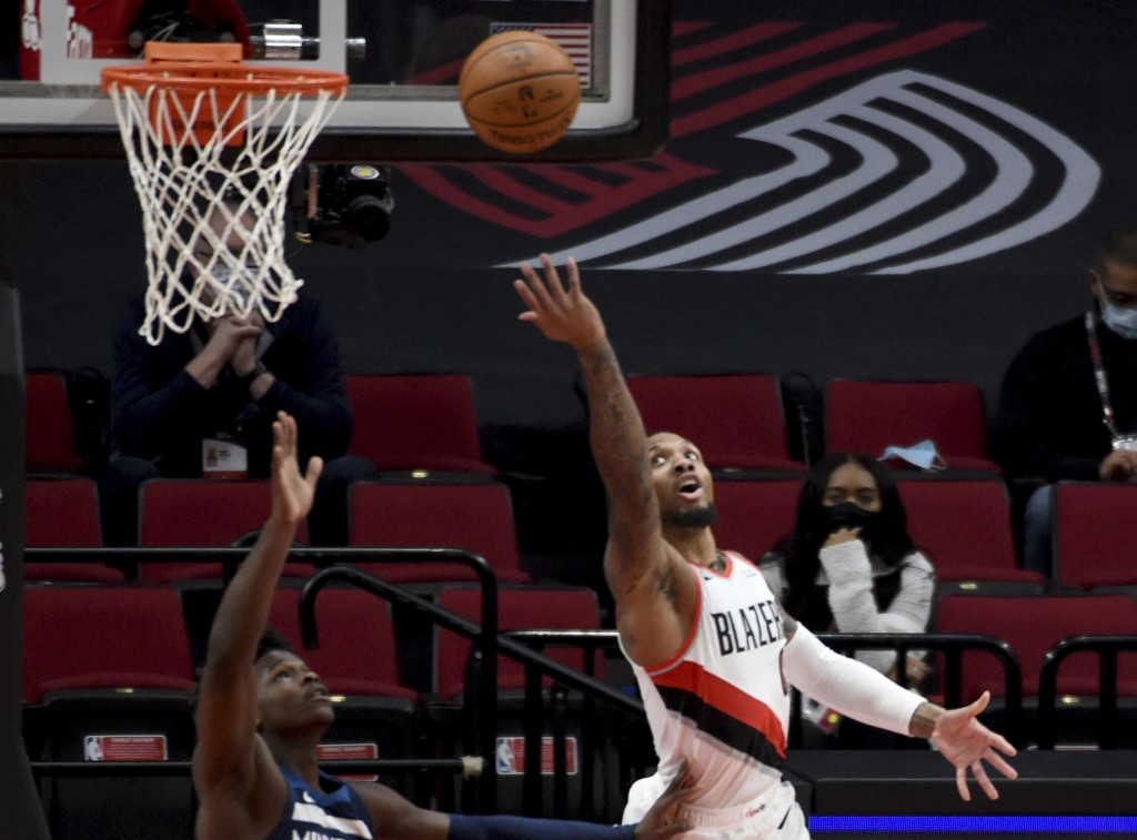 Portland Trail Blazers guard Damian Lillard, right, lays the ball in over Minnesota Timberwolves guard Anthony Edwards, left, during the first half of...