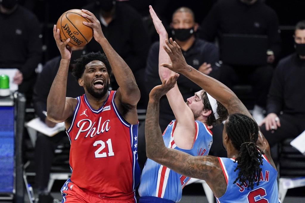 Philadelphia 76ers' Joel Embiid (21) shoots over Brooklyn Nets' Joe Harris (12) during the first half of an NBA basketball game Thursday, Jan. 7, 2021...