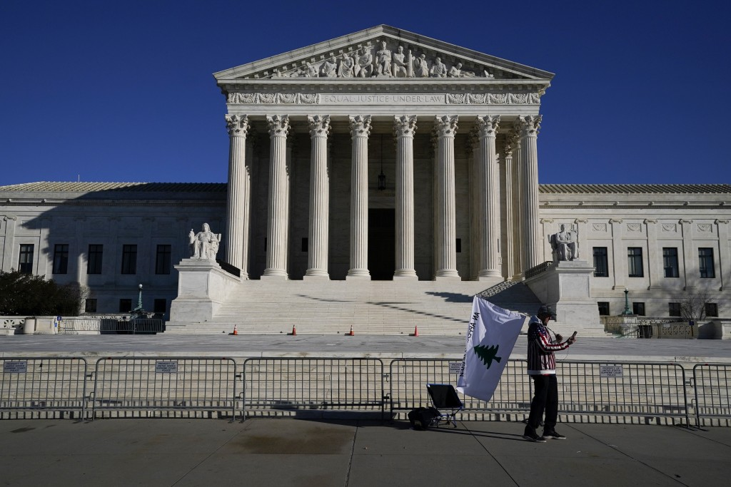 A person walks by newly-placed barricades around the Supreme Court Building, the day after violent protesters loyal to President Donald Trump stormed ...