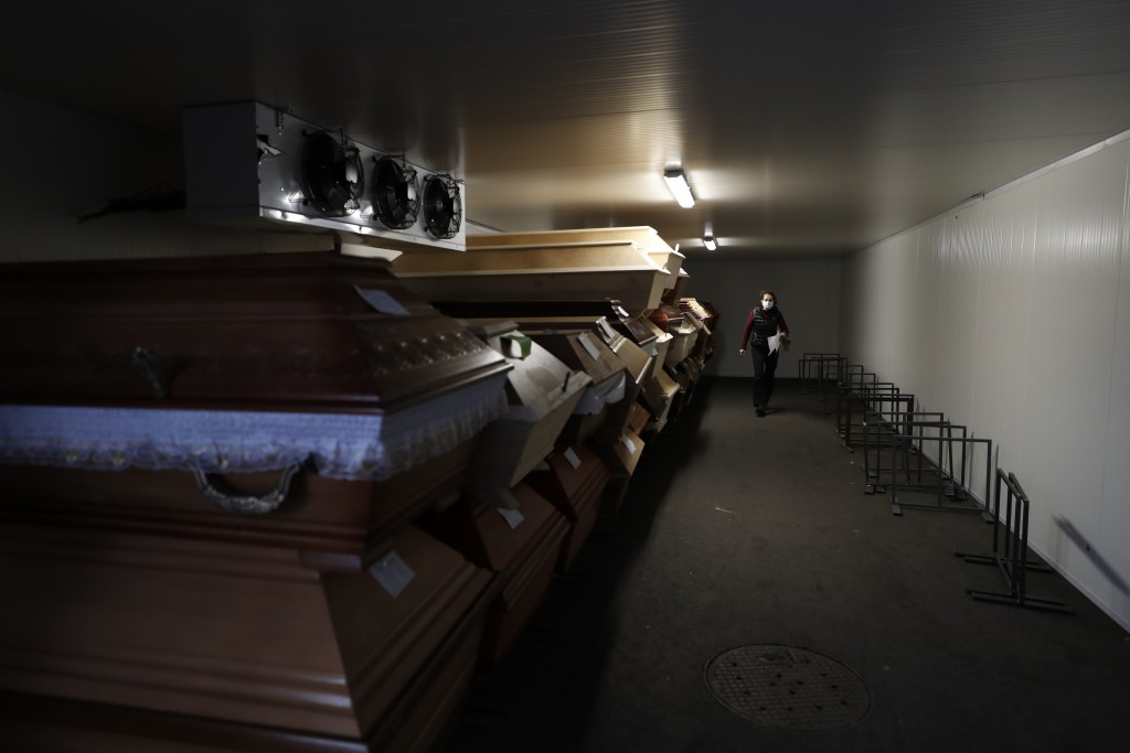 A worker walks past caskets placed inside an overflow cold storage container placed outside a crematorium in Ostrava, Czech Republic, Thursday, Jan. 7...
