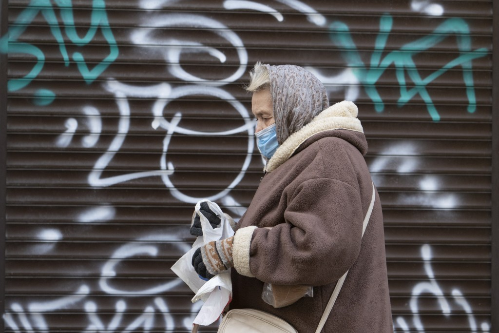 A woman wearing a face mask to protect against coronavirus walks past a closed shop in Ivano-Frankivsk, Western Ukraine, Friday, Jan. 8, 2021. Ukraine...