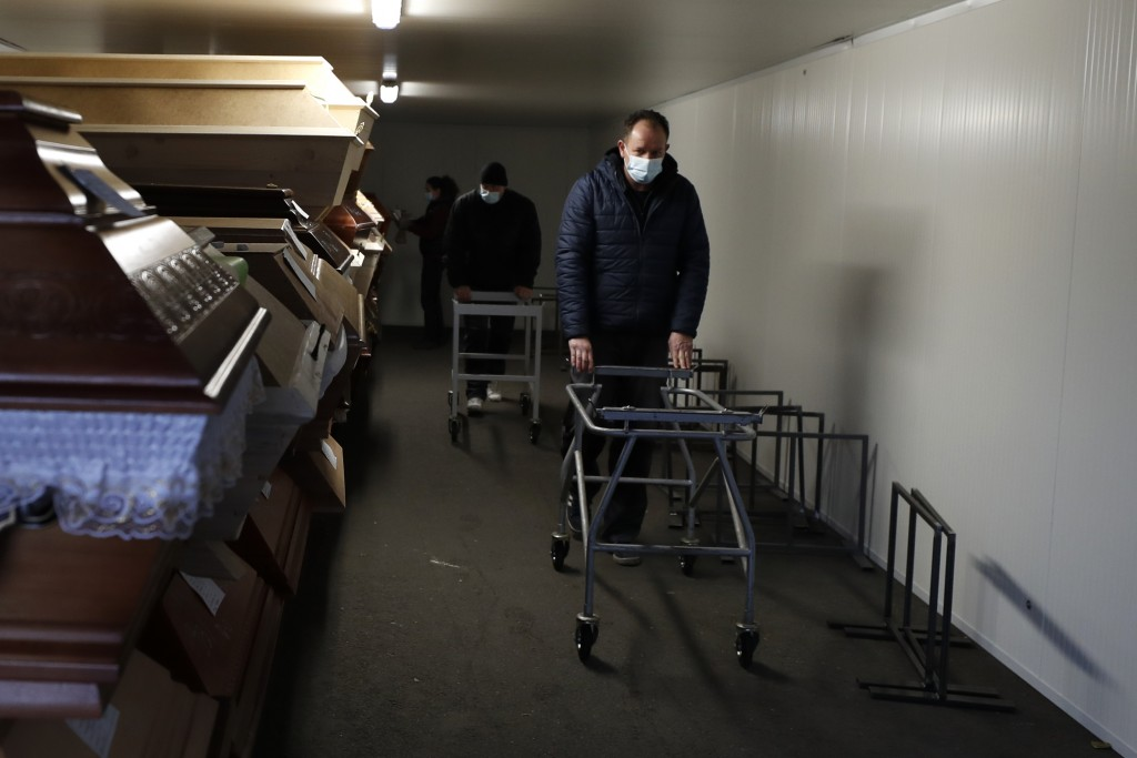 Workers walk past caskets placed inside an overflow cold storage container placed outside a crematorium in Ostrava, Czech Republic, Thursday, Jan. 7, ...