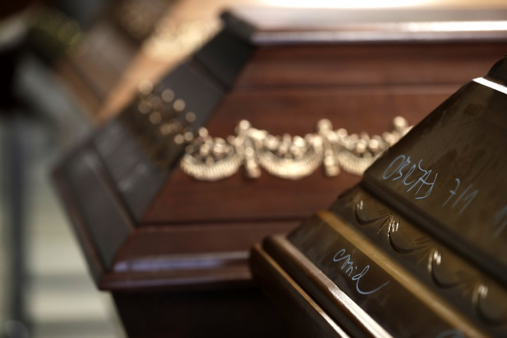 A casket, marked with COVID, is prepared to be incinerated at a crematorium in Ostrava, Czech Republic, Thursday, Jan. 7, 2021. The biggest crematoriu...