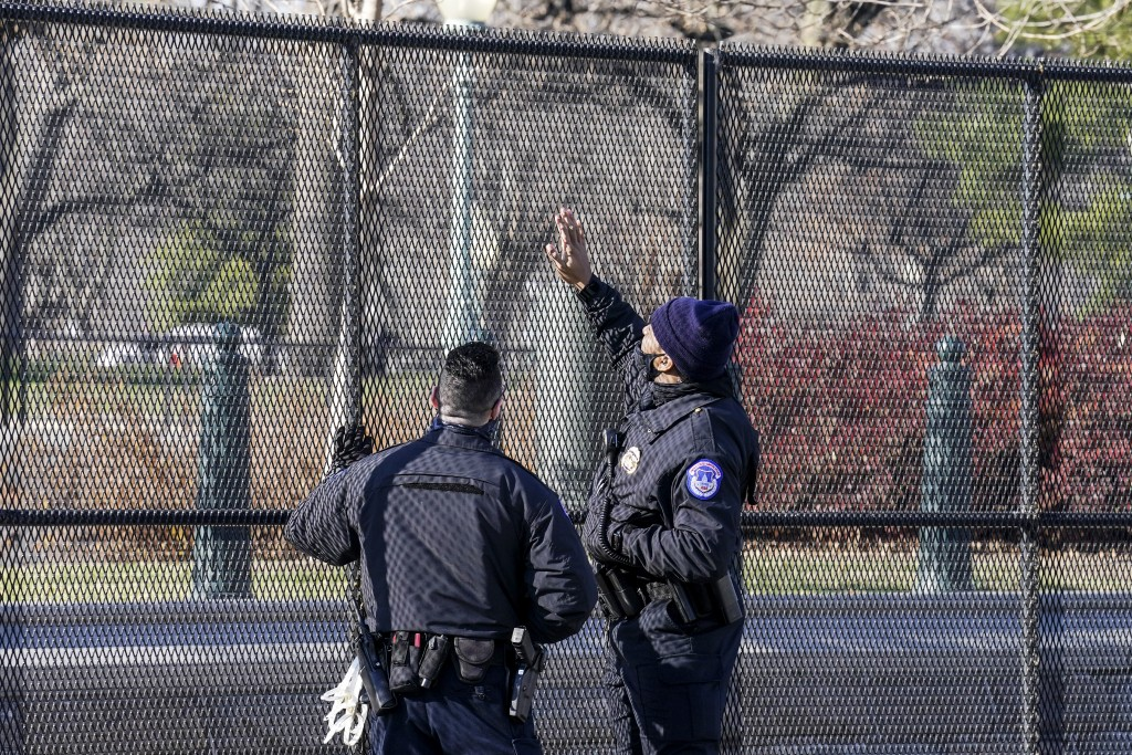 Capitol police officers look at fencing that was installed around the exterior of the Capitol grounds, Thursday, Jan. 7, 2021 in Washington. The House...