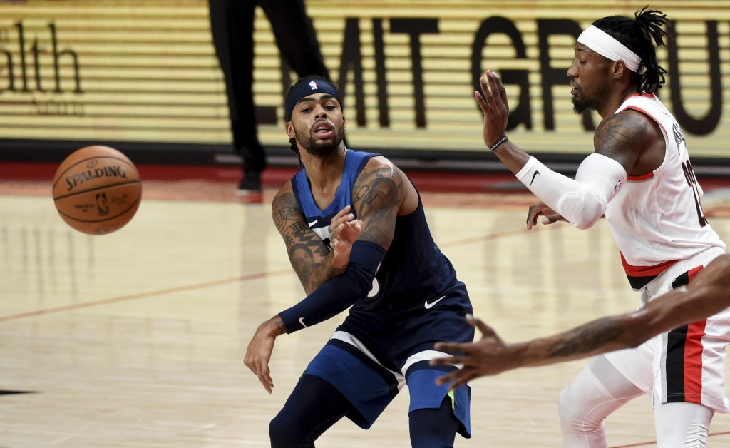 Minnesota Timberwolves guard D'Angelo Russell (0), left, passes the ball as Portland Trail Blazers forward Robert Covington (23), right, defends durin...