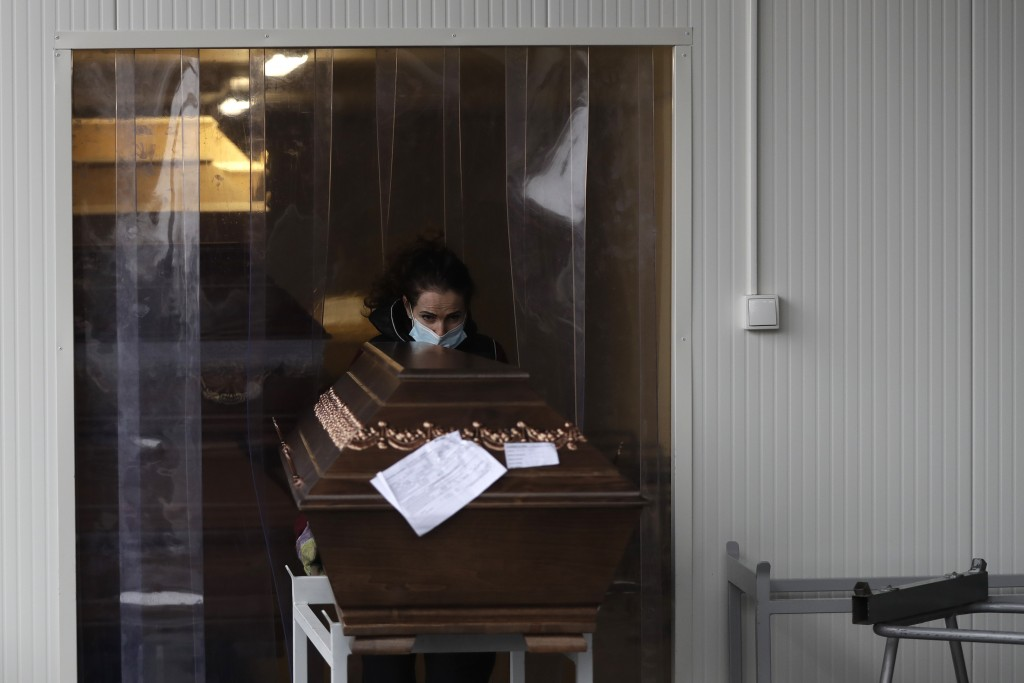 A worker moves a casket into an overflow cold storage container placed outside a crematorium in Ostrava, Czech Republic, Thursday, Jan. 7, 2021. The b...