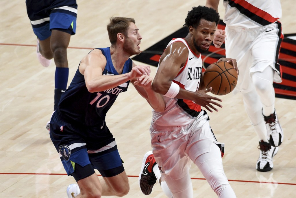Portland Trail Blazers guard Rodney Hood, right, drives to the basket against Minnesota Timberwolves forward Jake Layman, left, during the first half ...