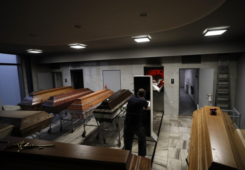 A worker moves a casket to be incinerated at a crematorium in Ostrava, Czech Republic, Thursday, Jan. 7, 2021. The biggest crematorium in the Czech Re...