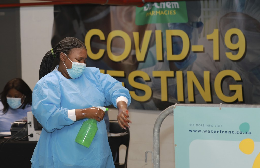 A health-care worker sanitises her hands before conducting COVID-19 tests at a Dis-Chem drive-through testing station at the V&A Waterfront in Cape To...