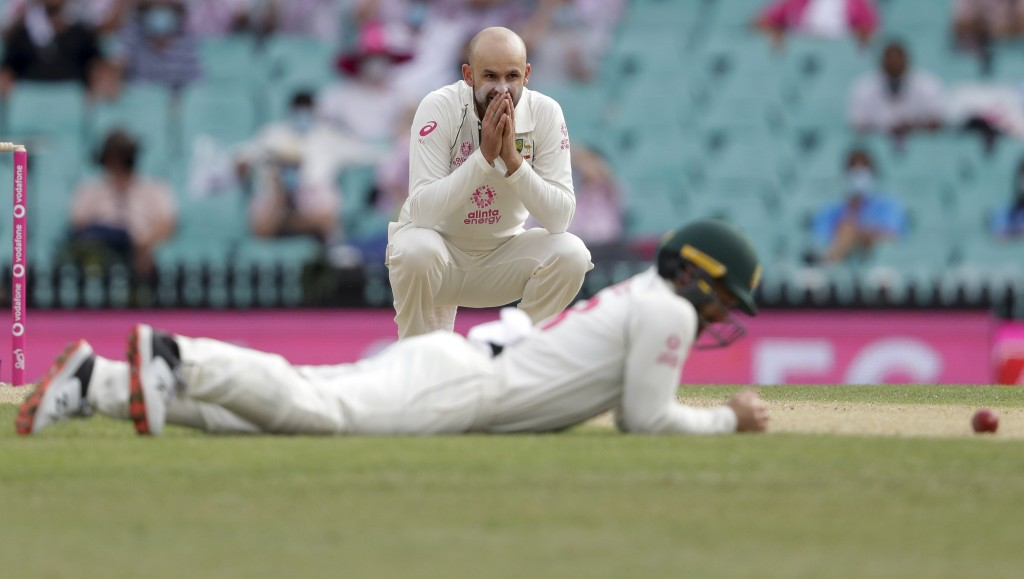 Australia's Nathan Lyon reacts as teammate Australia's Matthew Wade missed a catch opportunity during play on day two of the third cricket test betwee...
