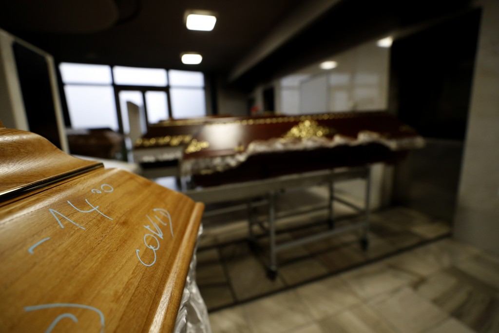 A casket, marked with COVID is prepared to be incinerated at a crematorium in Ostrava, Czech Republic, Thursday, Jan. 7, 2021. The biggest crematorium...