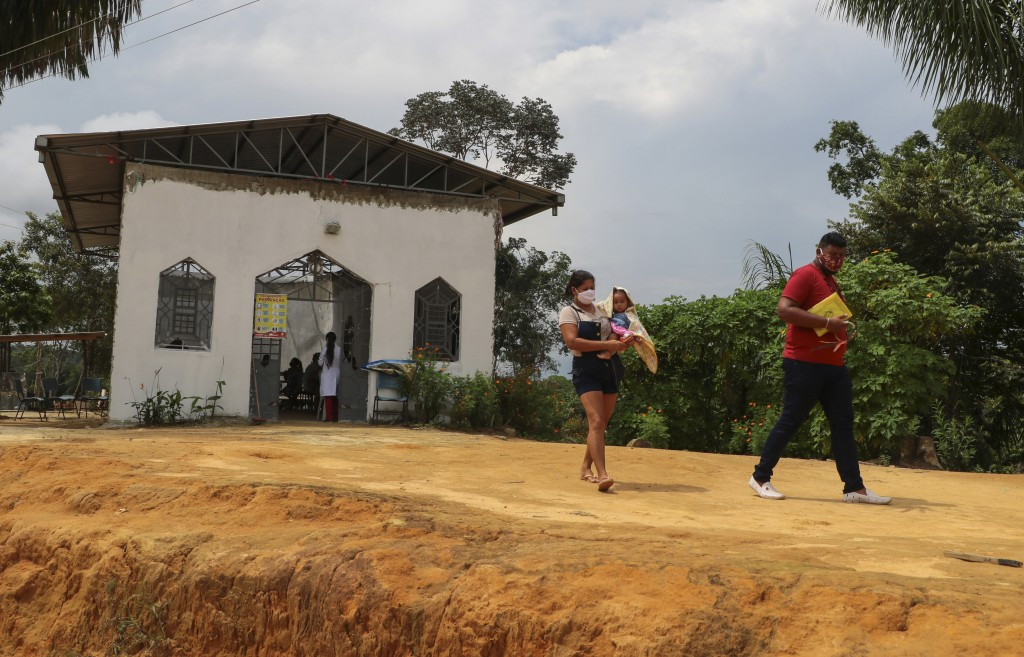 Icaro de Oliveira and his wife, of the Mura indigenous group, walk home after being tested for COVID-19 at the Indigenous Park, a tribal community in ...