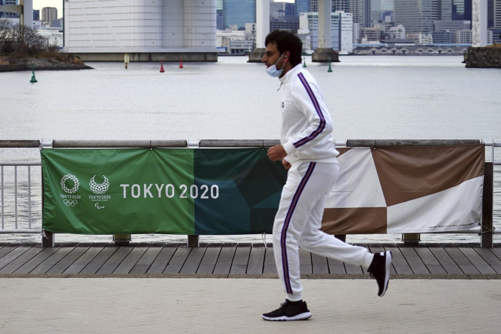 A man runs near a banner of the Tokyo 2020 Olympic and Paralympic games in the Odaiba section Friday, Jan. 8, 2021 in Tokyo. The senior member of the ...