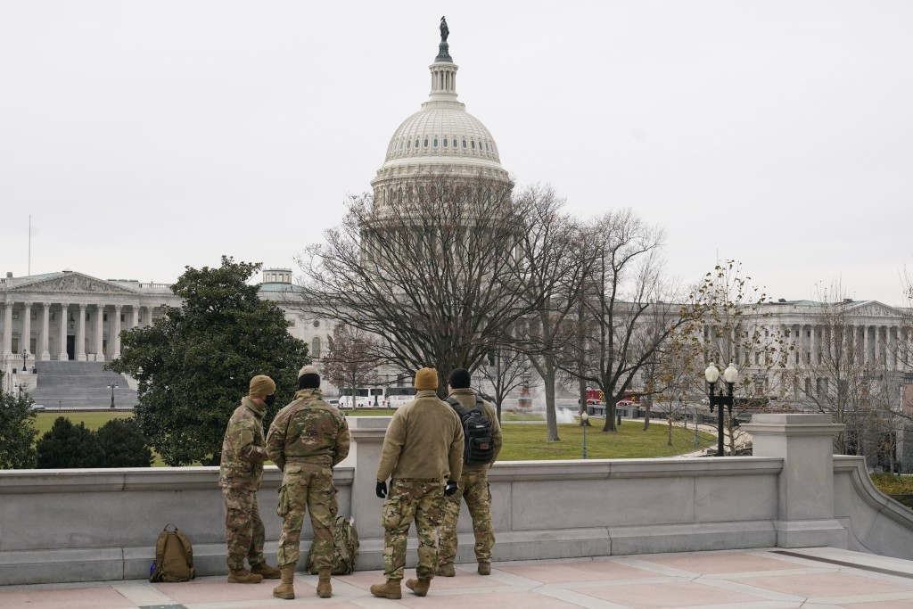 With the U.S. Capitol Building in view, members of the military stand on the steps of the Library of Congress' Thomas Jefferson Building in Washington...