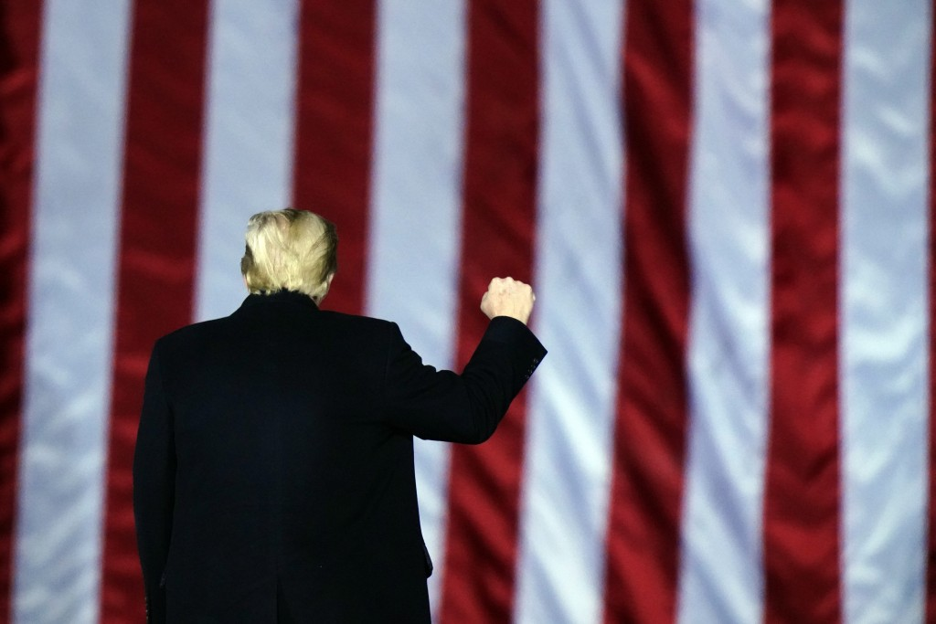 President Donald Trump gestures at a campaign rally in support of U.S. Senate candidates Sen. Kelly Loeffler, R-Ga., and David Perdue in Dalton, Ga., ...