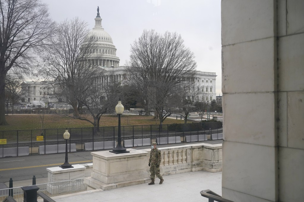 With the U.S. Capitol Building in view, a member of the military stands guard outside Russell Senate Office Building on Capitol Hill in Washington, Fr...