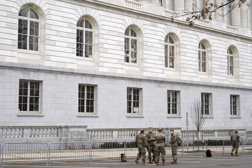 Members of the military stand guard outside Russell Senate Office Building on Capitol Hill in Washington, Friday, Jan. 8, 2021, in response to support...